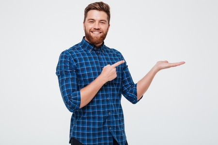 Foto de Excited smiling bearded man pointing finger at copy space on his palm isolated over white background - Imagen libre de derechos