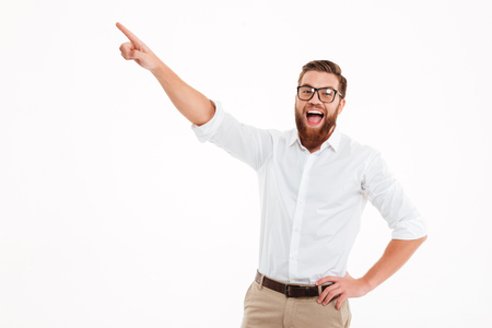 Foto de Happy excited bearded man in eyeglasses pointing finger away at copy space isolated over white background - Imagen libre de derechos