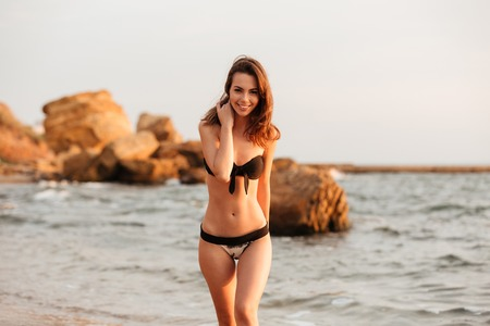 Photo for Smiling brunette woman in bikini walking on beach and looking at the camera - Royalty Free Image