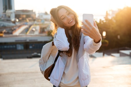 Photo pour Happy brunette woman in autumn clothes making selfie on smartphone outdoors - image libre de droit