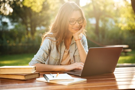 Photo for Smiling brunette woman in eyeglasses sitting by the table in park with books and using laptop computer - Royalty Free Image