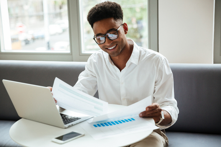 Photo for Picture of happy young african man sitting coworking by laptop computer holding documents. Looking aside. - Royalty Free Image
