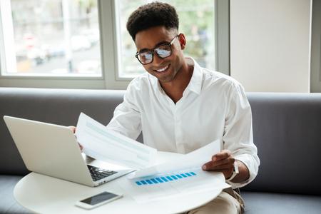 Foto de Picture of happy young african man sitting coworking by laptop computer holding documents. Looking aside. - Imagen libre de derechos