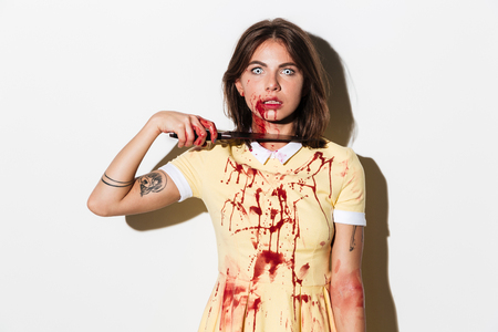Foto de Mad creepy zombie woman cutting her throat with a knife and looking at camera isolated over white background - Imagen libre de derechos