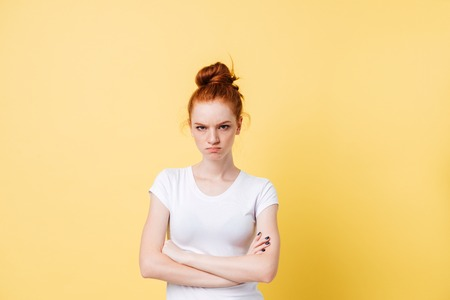 Photo for Angry ginger woman posing with crossed arms and looking at the camera over yellow background - Royalty Free Image