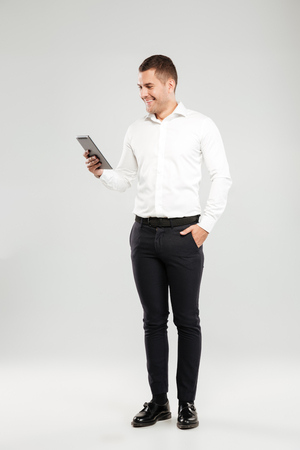 Foto de Image of smiling young man dressed in white shirt isolated over grey wall background. Looking aside chatting by tablet computer. - Imagen libre de derechos