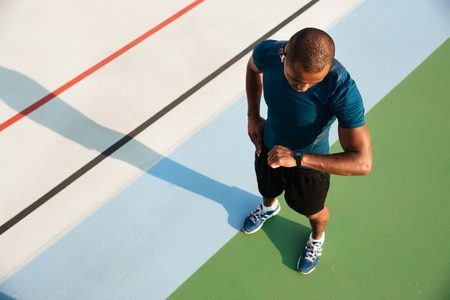 Foto de Top view of a young african sportsman looking at his wrist watch while standing on a track field - Imagen libre de derechos