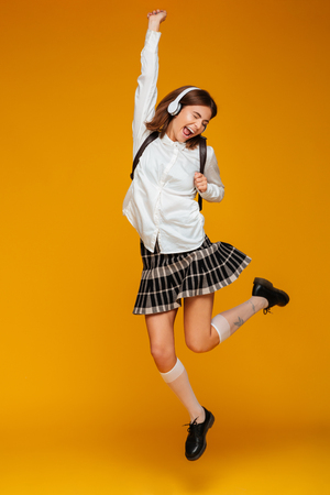 Photo for Full length portrait of a happy teenage schoolgirl in uniform with headphones jumping while listening to music isolated over orange background - Royalty Free Image