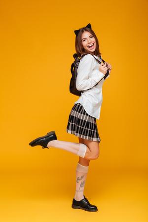 Foto de Full length portrait of a teenage schoolgirl in uniform with backpack standing and looking at camera isolated over orange background - Imagen libre de derechos