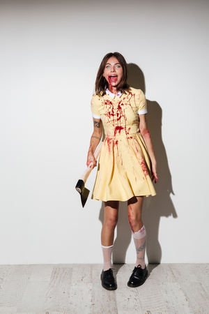 Photo pour Full length picture of mad happy zombie woman in dress holding an axe and looking at the camera over white background - image libre de droit