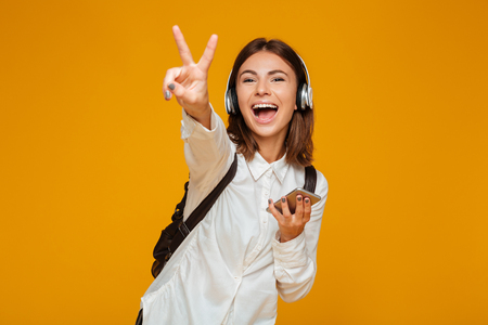 Photo for Portrait of a cheerful teenage schoolgirl in uniform with headphones holding mobile phone and showing peace gesture isolated over orange background - Royalty Free Image