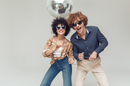 Foto de Image of young emotional smiling retro loving couple standing and posing isolated. Looking camera dancing near disco ball. - Imagen libre de derechos