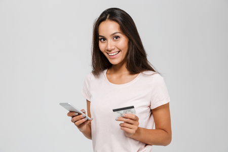 Photo pour Portrait of a smiling happy asian woman holding credit card and mobile phone while looking at camera isolated over white background - image libre de droit