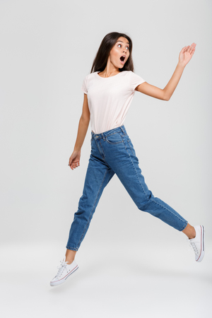 Foto de Full length portrait of an excited pretty asian woman jumping and looking away isolated over white background - Imagen libre de derechos