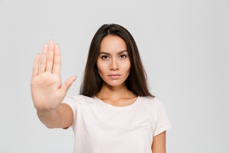 Foto de Portrait of a serious young asian woman standing with outstretched hand showing stop gesture isolated over white background - Imagen libre de derechos