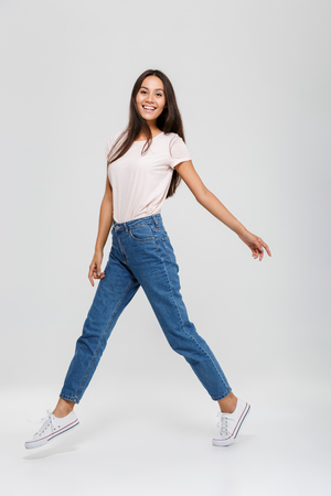 Photo pour Full length portrait of a casual young asian woman jumping and looking at camera isolated over white background - image libre de droit