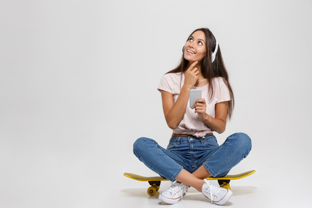 Photo pour Portrait of thinking young woman in white headphone holding mobile phone, sitting on skateboard, looking up, isolated over white background - image libre de droit