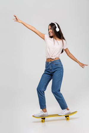Photo pour Full length portrait of a happy funny asian woman in headphones listening to music while riding on a skateboard isolated over white background - image libre de droit