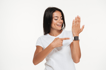 Photo pour Portrait of a happy young woman pointing finger at smart watch on her wrist isolated over white background - image libre de droit