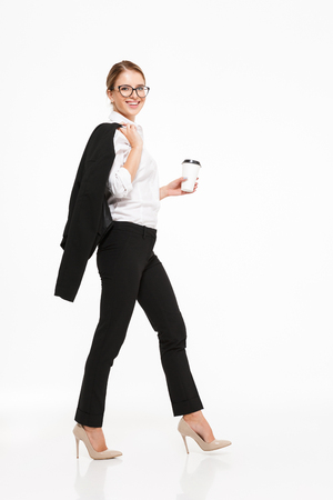 Photo for Full length side view image of smiling blonde business woman in eyeglasses walking in studio with cup of coffee and looking at the camera over white background - Royalty Free Image