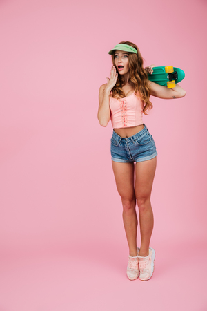 Photo for Full length portrait of a shocked astonished woman in summer clothes posing and holding hand at her face while standing with a skateboard isolated over pink background - Royalty Free Image