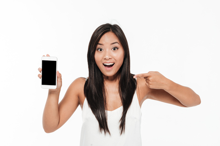 Photo pour Portrait of an excited happy casual asian woman holding and pointing finger at blank screen mobile phone isolated over white background - image libre de droit