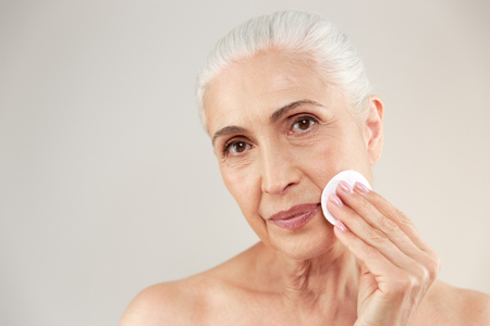 Foto de Beauty portrait of a lovely half naked elderly woman removing make-up with a cotton pad isolated over white background - Imagen libre de derechos