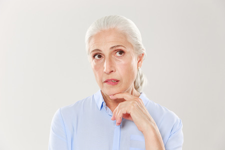 Photo for Close-up of thinking beautiful old woman in blue shirt, looking up, isolated over white background - Royalty Free Image