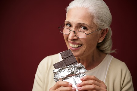 Foto de Image of happy old woman sitting over dark red background eating chocolate. Looking camera. - Imagen libre de derechos