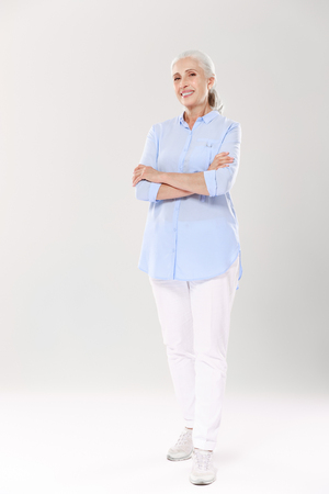 Photo for Full-length portrait of charming old lady in blue shirt and white pants, standing with crossed hands, isolated on white background - Royalty Free Image