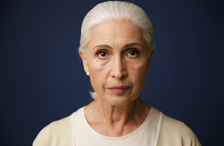 Photo pour Close-up portrait of beautiful old woman, over dark blue background - image libre de droit