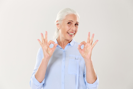 Foto de Portrait of smiling senior woman in blue shirt showing OK gesture, isolated on white background - Imagen libre de derechos