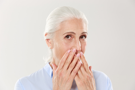 Photo pour Close-up portrait of charming old lady, covering her mouth with hands, looking at camera, isolated over white background - image libre de droit