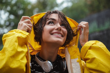 Foto de Close up portrait of a smiling pretty teenage girl with headphones wearing raincoat outdoors - Imagen libre de derechos