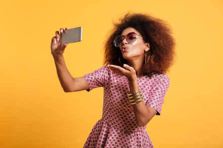 Foto de Portrait of a pretty young afro american woman in retro style clothes sending air kiss while standing and taking a selfie isolated over yellow background - Imagen libre de derechos