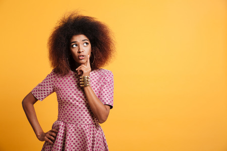 Photo pour Close-up portrait of retro stylish african thinking wooman touching her face, looking aside, isolated on yellow background - image libre de droit