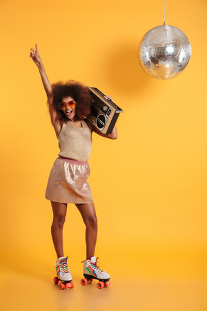 Photo for Full length portrait of happy afro american disco woman in sunglasses pointing with finger upward, standing on roller skates, holding boombox, looking at camera, isolated on yellow background - Royalty Free Image