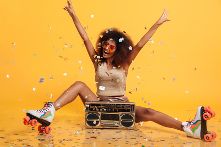 Photo pour Beautiful young african woman with afro hairstyle throwing confetti, showing peace gesture while sitting in roller skates with boombox, isolated on yellow background - image libre de droit