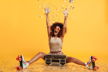 Photo pour Emotional african disko woman in retro wear and roller scates throwing confetti while sitting with boombox, isolated on yellow background - image libre de droit