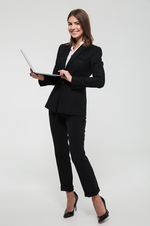 Photo pour Full length portrait of a confident smiling businesswoman in suit holding laptop computer and looking at camera isolated over white background - image libre de droit