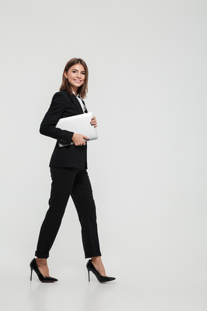 Photo pour Full length portrait of a confident pretty businesswoman in suit holding laptop computer while walking and looking at camera isolated over white background - image libre de droit