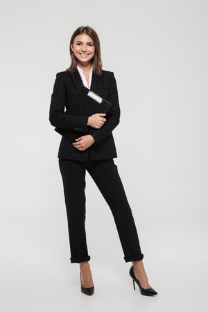 Foto de Full length portrait of a happy smiling businesswoman in suit holding clipboard and looking at camera isolated over white background - Imagen libre de derechos