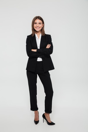 Photo pour Full length portrait of happy cheerful businesswoman in suit standing with arms folded and looking at camera isolated over white background - image libre de droit