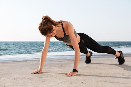 Foto de Photo of young female athlete standing in a plank position at the seaside - Imagen libre de derechos