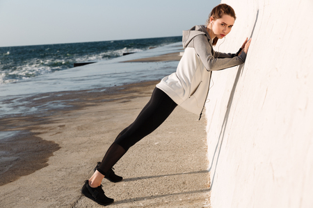 Foto de Full-length photo of  fit girl doing push-ups while standing near white wall, looking at camera, seaside outdoor - Imagen libre de derechos