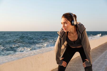 Photo pour Portrait of charming caucasian runner woman listening to music while resting after workout - image libre de droit