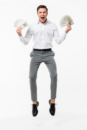 Foto de Full length portrait of a happy successful man in white shirt holding bunch of money banknotes while jumping and looking at camera isolated over white background - Imagen libre de derechos