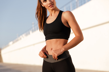 Foto de Cropped image of young fitness woman showing abs while training near sea - Imagen libre de derechos