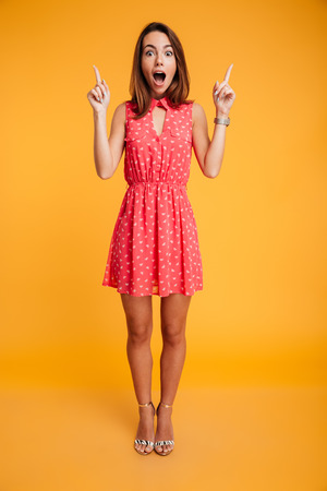 Photo pour Full length portrait of pretty surprised woman in red dress pointing with two fingers, looking at camera with open mouth, isolated on yellow background - image libre de droit