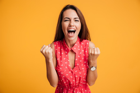 Foto de Happy successful young woman with raised hands shouting and celebrating success over yellow background - Imagen libre de derechos
